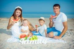 Familie mit Wassermelone auf dem Strand Stockbilder