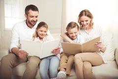 Familie mit zwei entzückenden Kindern, die zusammen zu Hause sitzen und Lesebüchern stockbild
