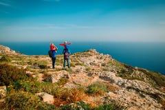 Familie mit zwei Kindern auf den Schultern, die in den Bergen wandern Lizenzfreies Stockbild