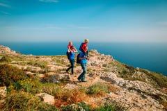 Familie mit zwei Kindern auf den Schultern, die in den Bergen wandern Lizenzfreie Stockfotografie