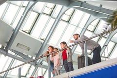 Familie mit zwei Kindern auf der Galerie im Flughafen stockfotos