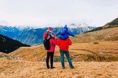 Familie mit zwei Kindern, die in den Winterbergen wandern lizenzfreie stockfotografie