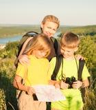 Familie mit zwei Kindern, die Karte, Familienreise betrachten Mutter und c stockbild