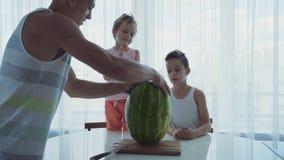 Familie mit zwei kleinen lustigen Kindern, die an einem Abendtische sitzen Vati schneidet eine große Wassermelone stock video footage