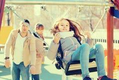 Familie mit zwei Mädchen, die Spaß auf Schwingen draußen haben lizenzfreie stockbilder