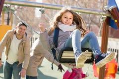 Familie mit zwei Mädchen, die Spaß auf Schwingen draußen haben stockfoto