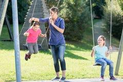 Familie mit zwei Mädchen und Mutter auf Spielplatz schwingen Lizenzfreies Stockfoto