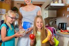 Familie - moeder die ontbijt voor school maakt Royalty-vrije Stock Foto's