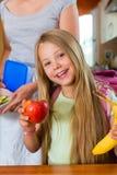 Familie - moeder die ontbijt voor school maakt Royalty-vrije Stock Afbeeldingen