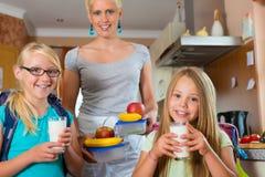 Familie - moeder die ontbijt voor school maakt Stock Afbeeldingen