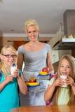 Familie - moeder die ontbijt voor school maakt Stock Foto's