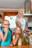 Familie - moeder die ontbijt voor school maken Stock Fotografie