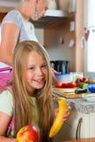 Familie - moeder die ontbijt voor school maken Stock Afbeelding