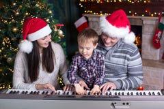 Familie - moeder, vader en jong geitje die santahoeden dragen die de piano over Kerstmisachtergrond spelen royalty-vrije stock foto