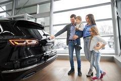Familie, neues schwarzes Auto im Ausstellungsraum beobachtend lizenzfreie stockfotos