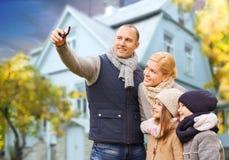 Familie nimmt Herbst selfie durch Mobiltelefon über Haus lizenzfreie stockfotografie