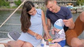 Familie novo da vela dentro no barco no loch, saindo os dentes no bebê que morde brinquedos fora, bom pai com mãe video estoque