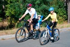 Familie op de fietsen in zonnig Stock Foto
