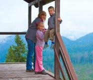 Familie op de houten portiek van het bergplattelandshuisje Stock Fotografie