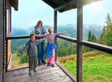 Familie op de houten portiek van het bergplattelandshuisje Stock Afbeeldingen