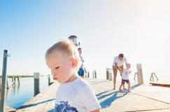 Familie op de pijler bij de vuurtoren, de zonnige zomer Stock Afbeelding