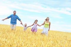 Familie op een tarwegebied royalty-vrije stock afbeelding