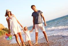 Familie op het strand bij zonsondergang royalty-vrije stock fotografie