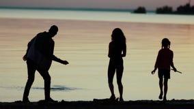 Familie op het strand bij zonsondergang Silhouetten van mannen, vrouwen en meisjes stock footage