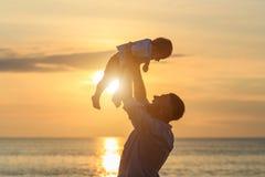 Familie op het strandconcept, Vader die en zijn zoon spelen vervoeren stock foto