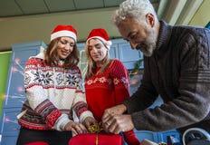 Familie op Kerstmisdag terwijl het voorbereiden van gift stock afbeeldingen
