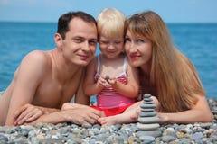 Familie op overzeese kust en piramide van stenen Stock Foto's
