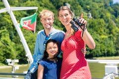 Familie op riviercruise met verrekijkers in de zomer stock foto's