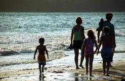 Familie op Strand bij Zonsondergang Stock Afbeelding