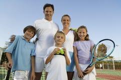 Familie op Tennisbaan door netto portret vooraanzicht stock afbeeldingen