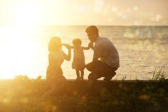 Familie openluchtpret in zonsondergang bij strand Royalty-vrije Stock Fotografie