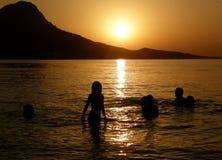 Familie in overzees bij zonsondergang royalty-vrije stock fotografie