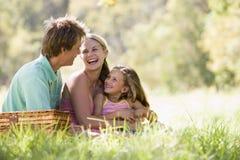Familie am Park, der ein Picknick und ein Lachen hat Lizenzfreie Stockfotografie