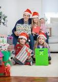 Familie in Santa Hats Holding Christmas Gifts Lizenzfreie Stockfotografie