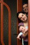 Familie schaut aus der Tür heraus Lizenzfreie Stockfotos