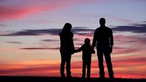 Familie silhouettiert Porträt an den Sonnenuntergang-, Elternteil- und Kindergriffhänden, unbesiegbar stock video footage