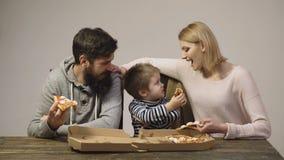 Familie sind in Verbindung stehen und köstliche Pizza essend Konzept von Nahrung Geschmackvolle Pizza Mutter, Vati und Sohn essen stock video