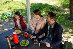 Familie sitzen durch die Tabelle im hölzernen Gazebo im Park beim Schauen auf der linken Seite stockfoto