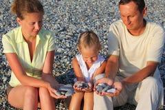 Familie sitzt in den pebbly Strand- und Holdingkieseln Stockbild