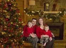 Familie sitzt neben Weihnachtsbaum Stockbilder