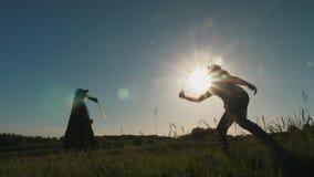 Familie speelbadminton op zonsondergangachtergrond stock videobeelden