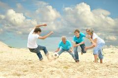 Familie speelvoetbal op een strand Stock Afbeeldingen