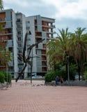 Familie spielende und Fütterungspidgeons nahe bei Skulptur in Barcelona stockbild