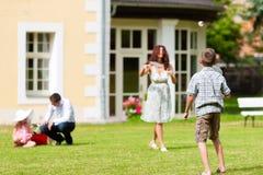 Familie spielt im Sommer vor ihrem Haus Lizenzfreie Stockfotografie