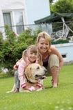 Familie spielt mit einem Hund einen Rasen am Haus Lizenzfreie Stockfotografie