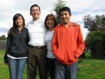 Familie steht auf Gras gegen Haus Lizenzfreies Stockfoto